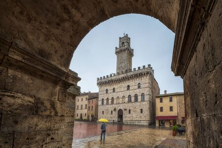 Tourist with yellow umbrella walks through empty medieval Grande Square - main square in Montepulciano, Italy with Palazzo Comunale (City Hall)
