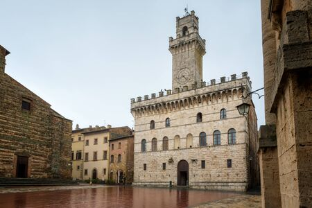 Rainy view of empty medieval Piazza Grande - main square in Montepulciano, Italy with Palazzo Comunale (Town Hall)