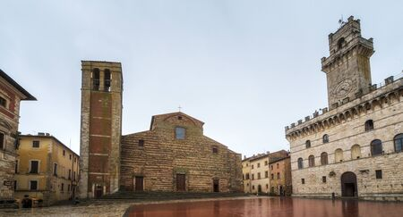 Rainy view of empty medieval Piazza Grande - main square in Montepulciano, Italy with Cathedral of Santa Maria Assunta and Palazzo Comunale (Town Hall).