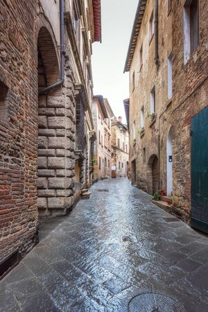 Amazing view with a narrow picturesque medieval street of old town of Montepulciano in Tuscany, Italy