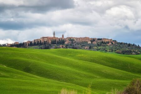 Amazing spring landscape with green rolling hills and old town of Pienza in the distance, Tuscany, Italy