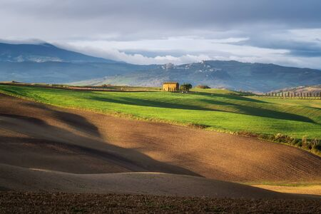 Amazing spring landscape with green rolling hills and farm houses in the heart of Tuscany in morning 写真素材