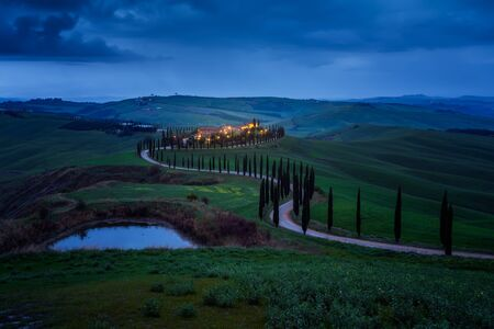 Amazing spring landscape with green rolling hills, cypresses and farm house in the heart of Tuscany after sunset