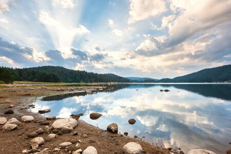 Beautiful morning view with dramatic sky over a mountain lake. Shiroka Polyana dam in Rhodopi Mountains, Bulgaria.