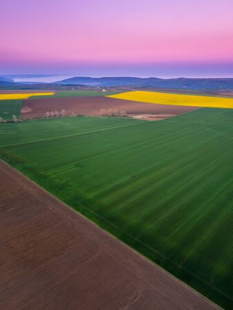 Aerial view of beautiful countryside with green and yellow spring fields. Blossoming rapeseed field with strips of bright yellow rape and and wheat in golden hour before sunset. 写真素材