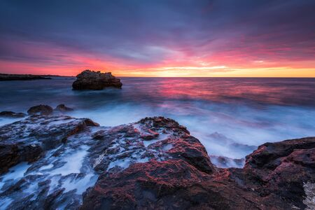 Stormy sea with colorful sunrise sky at the rocky coastline of the Black Sea Imagens