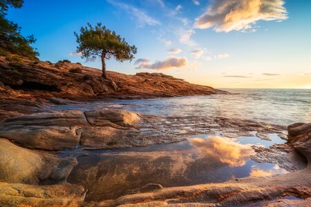 Magnificent sunset view with beautiful reflections at the rocky coastline of Thasos island, Greece