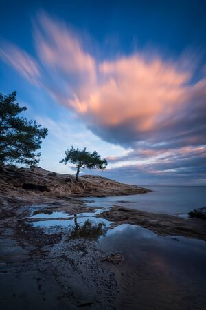 Magnificent long exposure sunset view with beautiful reflections at the rocky coastline of Thasos island, Greece