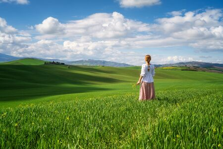 Rear view of a woman with vintage clothes admires the beauty of green rolling hills in the heart of Tuscany, Italy.