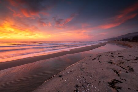 Amazing view with colorful reflections on a sandy beach at sunrise Imagens