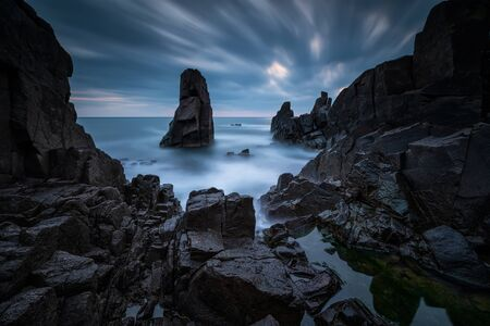 Amazing long exposure seascape with stunning rock formation in the blue hour before sunrise Imagens