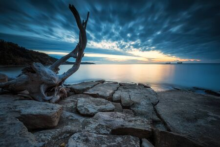Amazing long exposure seascape with rocky beach at sunrise in the blue hour