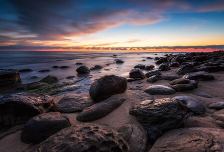 Amazing colorful seascape with rocky beach at sunrise