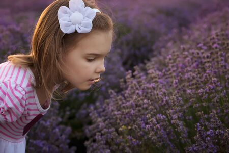 Portrait of a pretty girl enjoying the scent of a blossomed lavender field