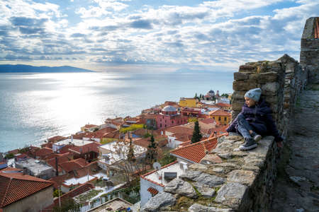 Little girl enjoys the view from the fortress of the old city of Kavala to the Aegean islands, northern Greece 報道画像