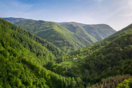 Aerial view with spring green forests and hills overgrown with lush vegetation and a small hut nestled between them, Balkan Mountains, Bulgaria