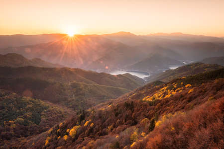 Beautiful panoramic skyline autumn view with colorful sunrise above an autumn forest in Rhodope Mountains, Bulgaria.