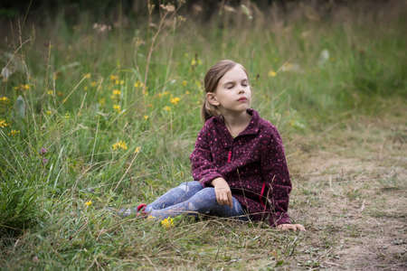 Lovely little girl playing in the summer field