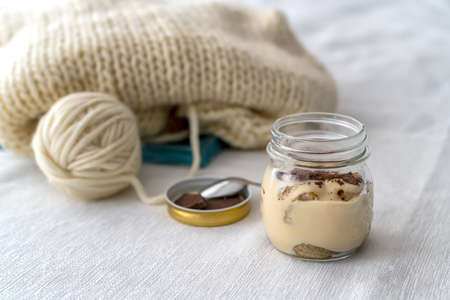 Gray knitting needles with a knit of thick woolen yarn and a jar of turamisu on a white background with a soft focus.Female hobby and leisure knitting concept.