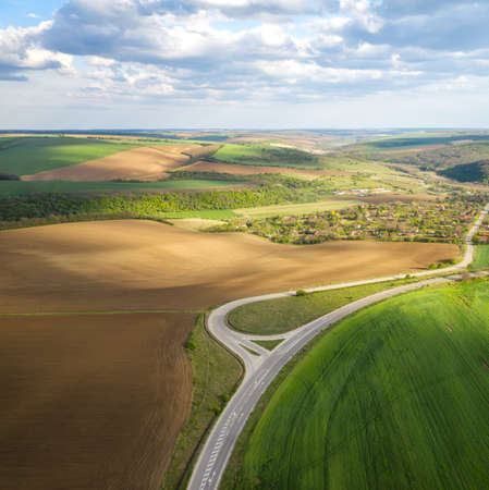 Aerial view of spring agriculture field and a road through it