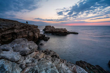 Amazing view with colorful sunrise sky and a silhouette of a photographer at the rocky coastline of the Black Sea