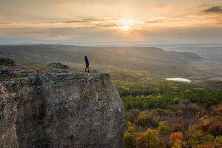 Silhouette of a woman on the top of a rock enjoys the view of sunset over an autumn forest 免版税图像