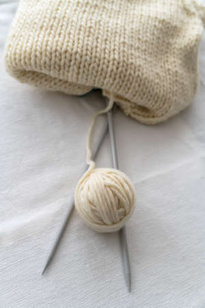 Grey knitting needles with knitting made thick wool yarn on white background with soft focus. Female hobby and leisure knitting concept.