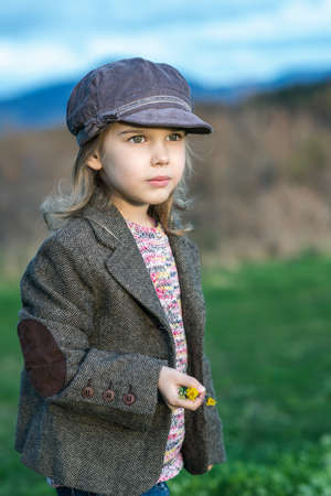 Lovely little girl with vintage clothes enjoying the spring sun among a spring green field