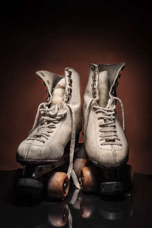 Old heavily used worn-out pair of white roller skates with some dirt and untied detailed shoelace buckles on reflective surface and warm brown background