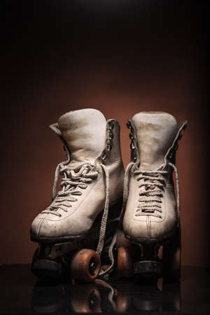 Old heavily used worn-out pair of white roller skates showing their boot tongues with some dirt and untied shoelace on reflective surface and warm brown background with upper space for titles