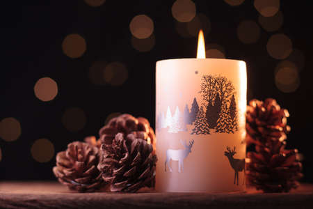 White Christmas candle and small brown pine cones on a wooden table with garlands background