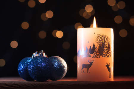White Christmas candle and blue shiny balls on a wooden table with garlands background