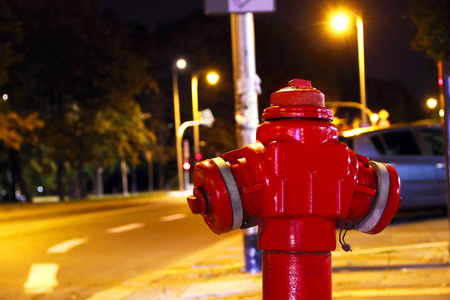 lonely red fire hydrant in the middle of a night street near the road, concept. Fire hydrant for emergency fire access. Stock Photo