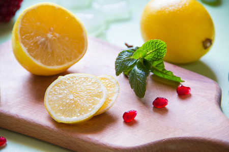 Lemon with pomegranate and mint is cut on a wooden board