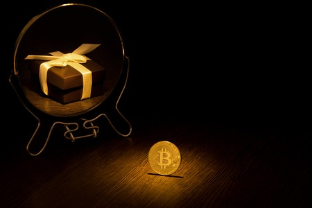 Golden Bitcoin Coin is displayed in a mirror in the form of a gift box with a ribbon, a business bitcoin concept on a black background.