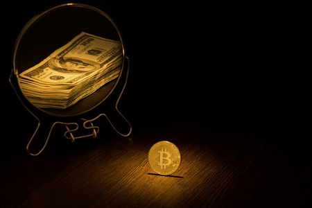 Golden Bitcoin Coin is displayed in a mirror in the form of a pack of one hundred dollar bills, a business bitcoin concept on a black background. Stock Photo