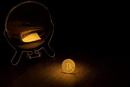 Golden Bitcoin Coin is displayed in a mirror in the form of a brown leather wallet with a pack of hundred dollar bills, a business bitcoin concept on a black background.