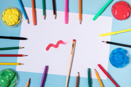 White sheet of paper on a blue background with copy space and place to inscribe around a color pen ink painters, brushes and pencils copy space. Brash is paint a red color paint