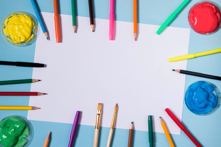 White sheet of paper on a blue background with copy space and place to inscribe a color around pen ink painters and brushes and pencils also copy space. Stock Photo
