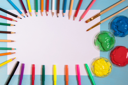 White sheet of paper on a blue background with copy space and place to inscribe around a color pen ink painters, brushes and pencils copy space. Brash is paint a red color paint. top view Stock Photo