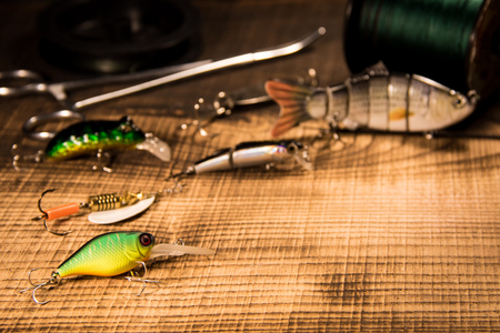 Fishing gear, artificial bait on a predator on a wooden background, top view wobblers and various bait cords and tongs with copyspace on a wooden background with .