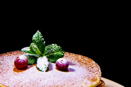 Red Berry cranberries lie on pancake with green mint sprinkled with powdered sugar on a black background. Stock Photo