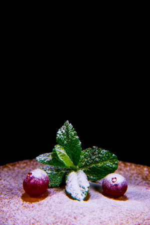 Berry cranberries lie on pancake with mint sprinkled with powdered sugar on a black background.