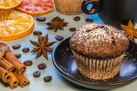Bestreut mit zuckerpulver schokolade cupcake auf einem schwarzen teller neben einer tasse kaffee, mit kaffeebohnen und zimt, orange gehackt Standard-Bild - 96281656