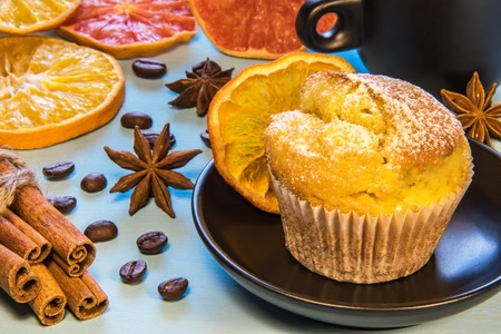 sprinkled with sugar powder cupcake on a black plate next to a cup of coffee, with coffee beans and cinnamon, chopped orange Standard-Bild