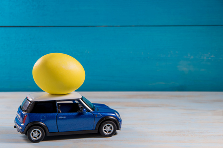 Easter egg in toy car on a blue background