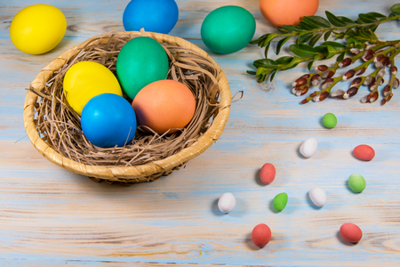 Easter eggs in a wooden basket, painted in different color on a blue background with a place for the inscription next to chokolate candy and green twigs