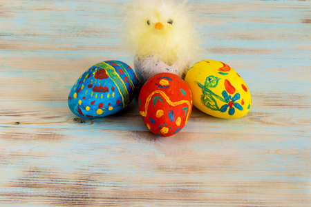Conceptual image of Easter with baby chicken next to eggs on blue wooden background with copyspace