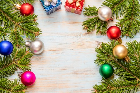 Frame from green branches of a Christmas tree with different multicolor toys and on a blue board with a place for the inscription Stock Photo