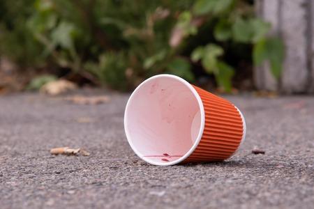 Papierglas auf Straßenverschmutzungskonzept Standard-Bild